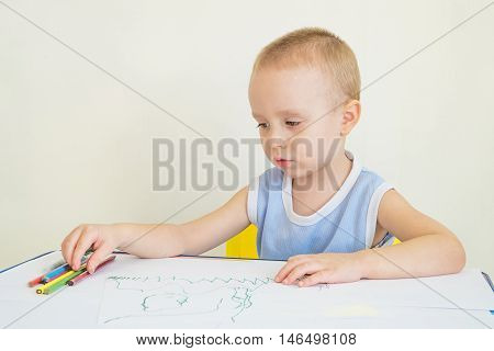 Little boy at a desk learning to draw with pencils. Child chooses a pencil.