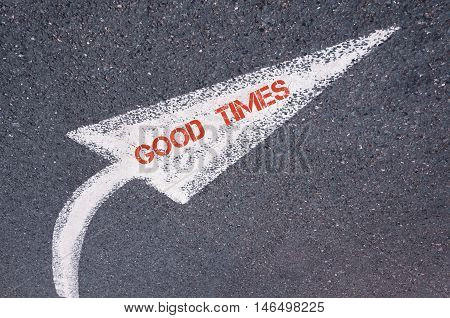 Directional White Painted Arrow With Words Good Times Over Road Surface