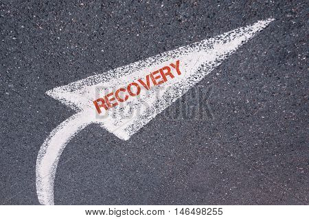 Directional White Painted Arrow With Word Recovery Over Road Surface