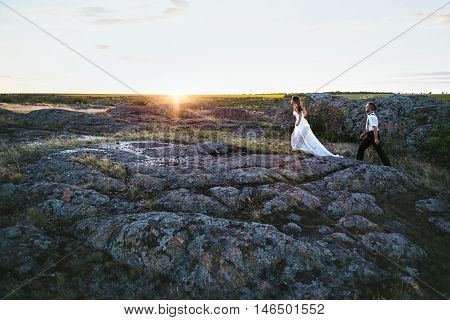 Bride and groom walk on rocky terrain in the background a beautiful sunset