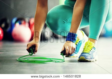 Young fit woman is taking jumping rope. Close up.