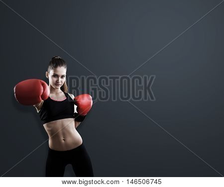 Woman boxer standing in room with black walls punching invisible opponent. Concept of competition. Mock up