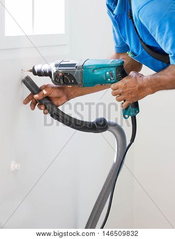 Man Drill On White Wall And Cleaning Dust With Vacuum Together