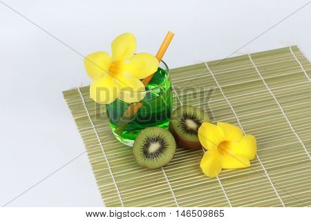 Two tone of kiwi juice served with halves kiwi and yellow flower on on bamboo.