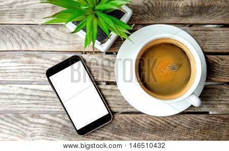 Smart phone and white coffee cup with flowerpot on wooden table.