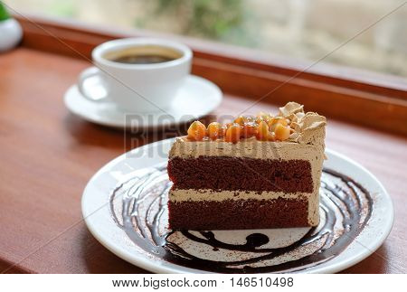 Macadamia chocolate cake with white coffee cup on wooden floor.