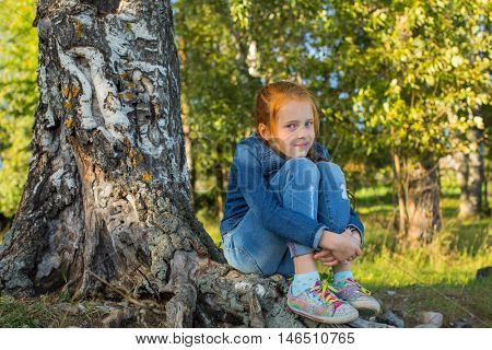 Little girl sitting on the roots of a birch.