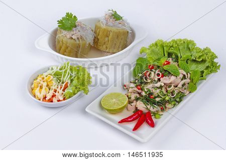 Spicy and sour mixed herb salad with pork and chicken served with side dish and mini vegetable salad and streamed gourd  wrap vermicelli and minced pork in bone soup.  Side view