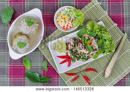 Spicy and sour mixed herb salad with pork and chicken served with side dish and mini vegetable salad and streamed gourd  wrap vermicelli and minced pork in bone soup.  Top view