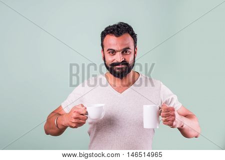 stylish Indian man with beard with two cups of coffee in two hand looking at camera.