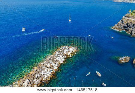 Blue Bay with a breakwater in the village Manarola. Cinque Terre. Italy. Liguria.
