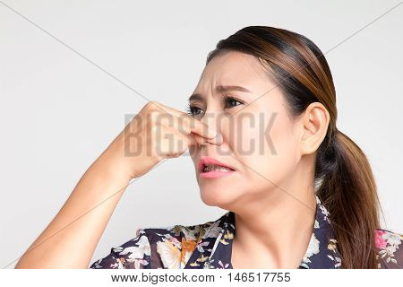 Asian woman closing her nose because she smelly