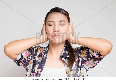 Asian woman covers his ears with his hands