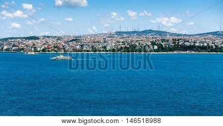 View from the European side of Istanbul across the Bosphorus to the Asian side of Istanbul. A ship is crossing the Bosphorus and the Maiden's Tower is on the left.