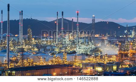 Oil refinery factory with mountain background at twilight