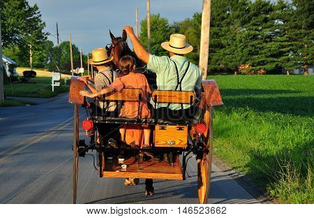 Lancaster County Pennsylvania - June 5 2015: Amish family riding along a rural road in their open horse and buggy carriage *