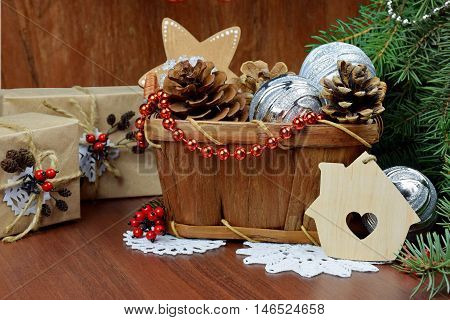 Christmas presents in a rustic style.Christmas or New Year greeting card with a wicker basket with pine cones fir branches wooden toys beads balls on the old wooden background vintage style selective focus.