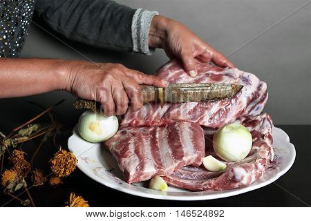 Female hand with hunter knife cutting a fresh pork meat dry flowers in the foreground focus on a hand. Studio shot