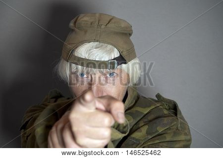 Female in camouflage uniform pointing a finger in a gun fashion concept of aggression horizontal studio shot