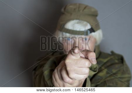 Woman with gray hair pointing a finger as it was a gun focus in the foreground horizontal studio shot