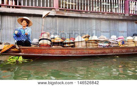Damnoen Saduak Thailand - March 21 2011 - Thai woman selling hats on a boat in Damnoen Saduak Floating Market
