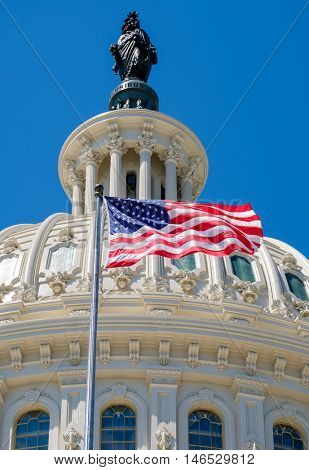 The United States flag waving in front of the Capitol dome in Washington D.C.