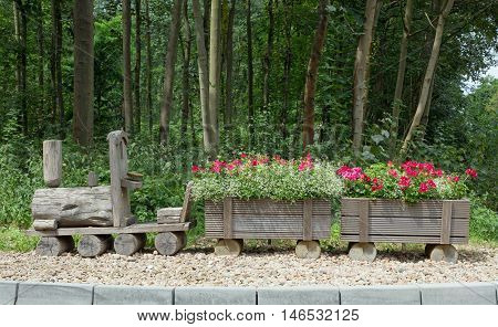 Wooden train with flowers on gravel, in the background trees