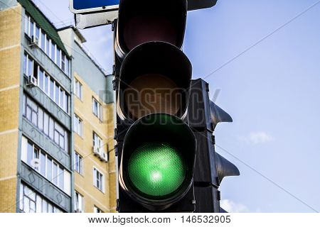 the green traffic signal against the background of the house