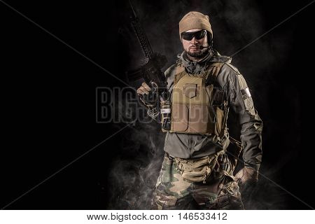 Special forces operator with assault rifle on black background