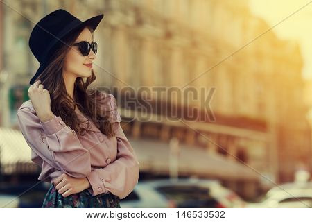 Outdoor portrait of young happy lady posing on street. Model wearing stylish clothes. Girl looking aside. Sunny day. Female fashion. City lifestyle. Toned style instagram filters. Copy space for text.