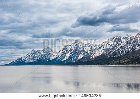 Grand Teton mountains with lake and dark, stormy cloudy, overcast, sky in national park