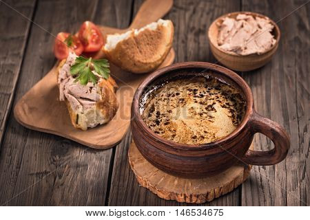 Mug of coffee and duck pate with bread rustic still-life
