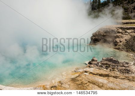 Light blue pool Excelsior geyser with steam rising from hot spring in Midway basin in Yellowstone National Park by Grand Prismatic