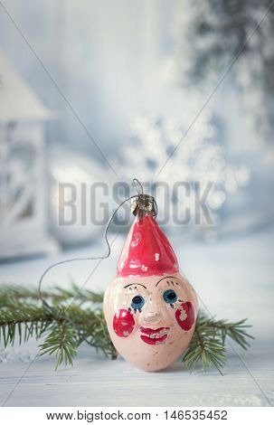 Old  Christmas clown decoration on light blue background.Toned