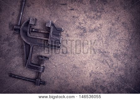 Old rusty vise tool on grunge metal surface with copy space.Toned