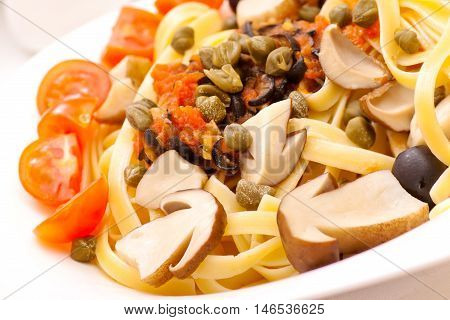 Pasta with mushrooms, capers and olives closeup