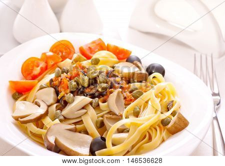 Pasta with mushrooms, capers and olives on plate