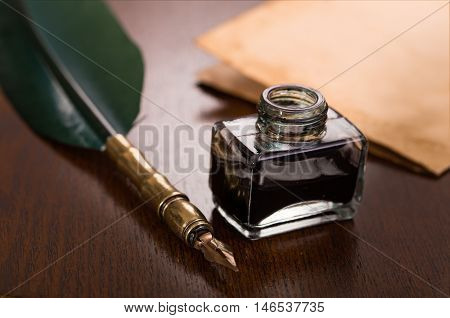 Quill pen, inkwell and paper on wooden table