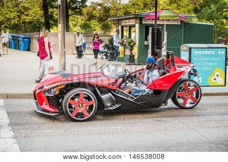 Chicago, USA - May 30, 2016: Man with cubs shirt in flashy red Polaris Slingshot Ferrari sports car on downtown street