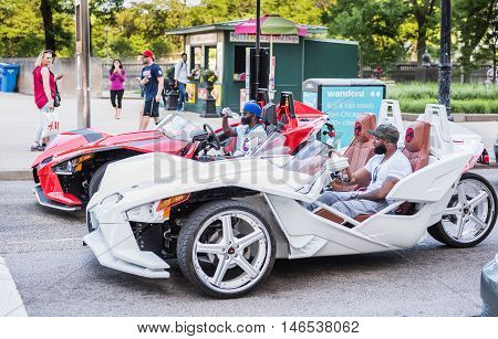 Chicago, USA - May 30, 2016: Two men with cubs shirt in flashy red and white Polaris Slingshot Ferrari sports cars on downtown street