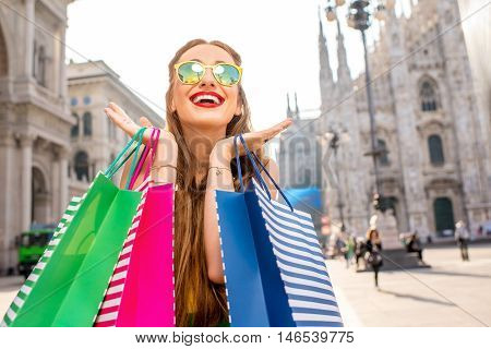Young woman with colorful shopping bags standing on the main square in front of the famous duomo cathedral in Milan. Happy shopping weekend in Milan