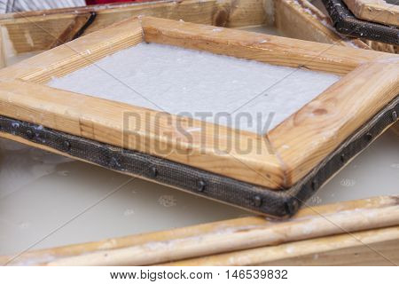A traditional method of making paper from pulp with a screen