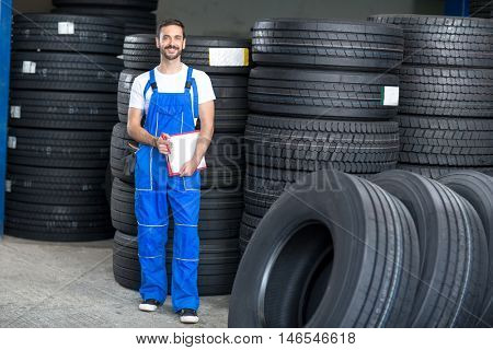 smiling mechanic checing clipboard car tires in tire store