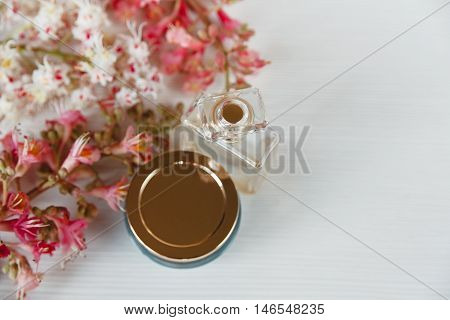 There White and Pink  Branches of Chestnut Tree,Jar of Cream and Bottle of Parfum are on White Table,Top View,Background