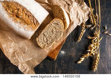 Fragrant fresh-baked rye bread on a black wooden table. Bread is sliced. Spikelets of wheat and rye close. Rustic Style. Top view