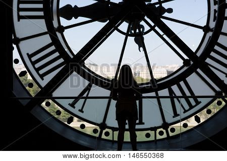 Clock at the Musee D'Orsay in Paris France. In the back we see the Sacre Coeur Basilica in Montmatre