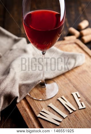 Glass of red wine on wooden board with kitchen towel and with letters and corks. Great for bar and restaurant. Still Life Photography