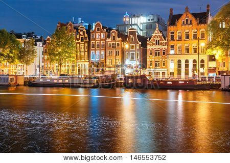 Amsterdam canal Amstel with typical dutch houses, houseboat and luminous track from the boat at night, Holland, Netherlands.