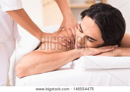 Close up of masseuse hands massaging male shoulder gently. Man is lying on table with enjoyment