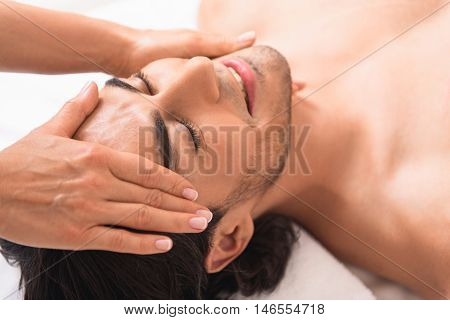 Relaxed young guy is enjoying massage at spa. He is resting and smiling. Masseuse is touching his forehead and chin